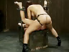 Brunette girl tied with metal frame getting her pussy fisted both hole fucked with strapon by mistress asshole fingered by master in the dungeon