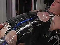 Blonde cross dresser in latex tied up, wrapped up and tortured